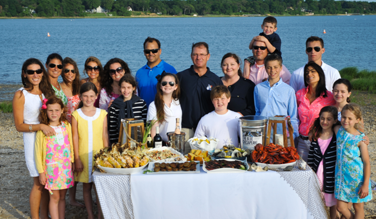 Schultzy with family of people gathered around a clambake table at the beach