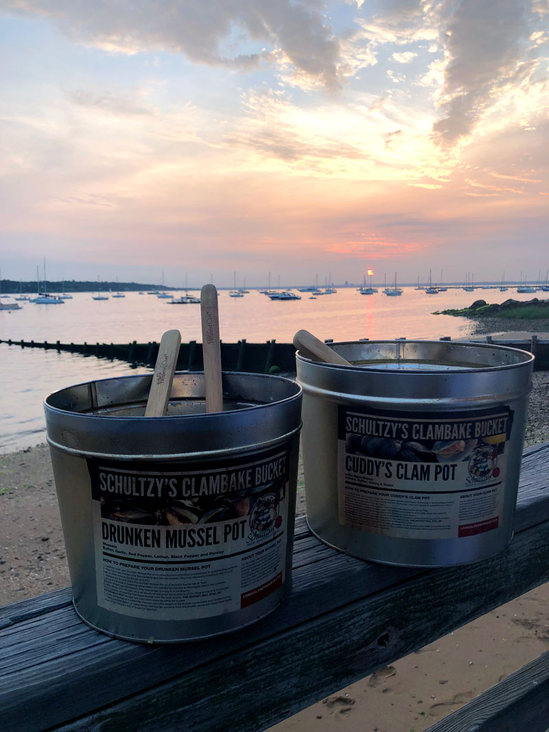two-schultzys-clambake-buckets-sitting-on-a-ledge-in-front-of-a-beautiful-sunset